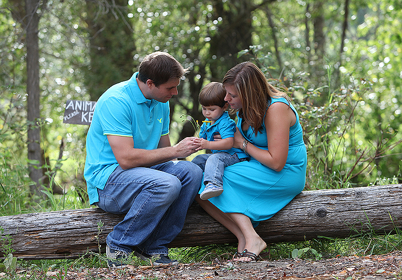 family of 3 wearing blue and jeans sitting on a log in the forest