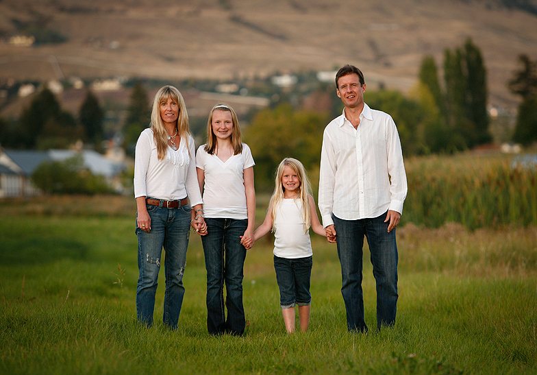 family of 4 wearing white shirts standing in a farmers' field