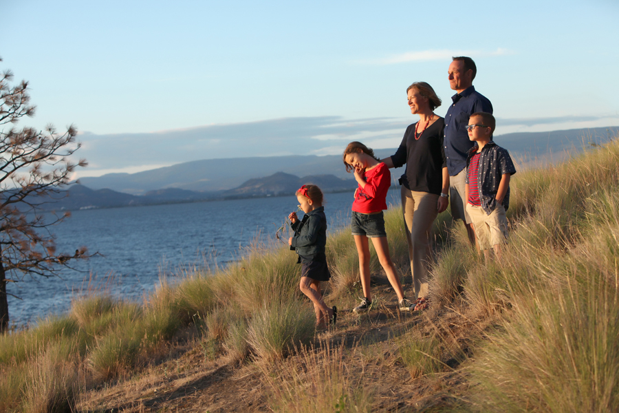 Photo of family of 5 standing on a hill of dried grass by lake and mountains