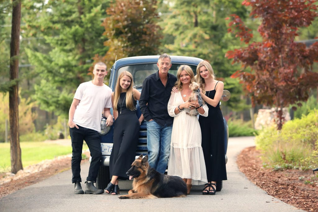 family of 5 wearing black, blue and white standing with their dog in front of a vintage truck on a driveway with trees