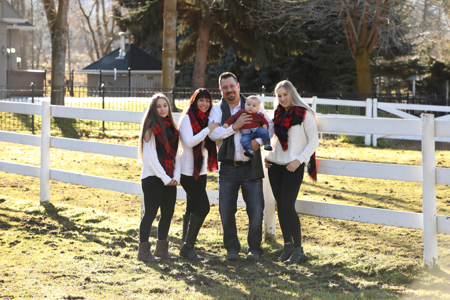 family of 5 wearing white and red plaid hold baby boy in front of a white horse fence