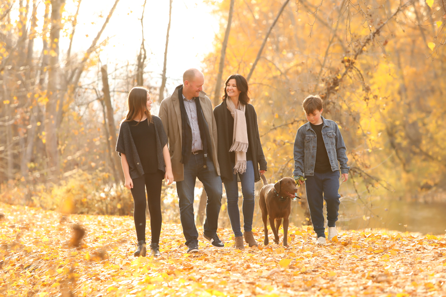 family of 4 walk with dog on a path of orange autumn leaves in a forest