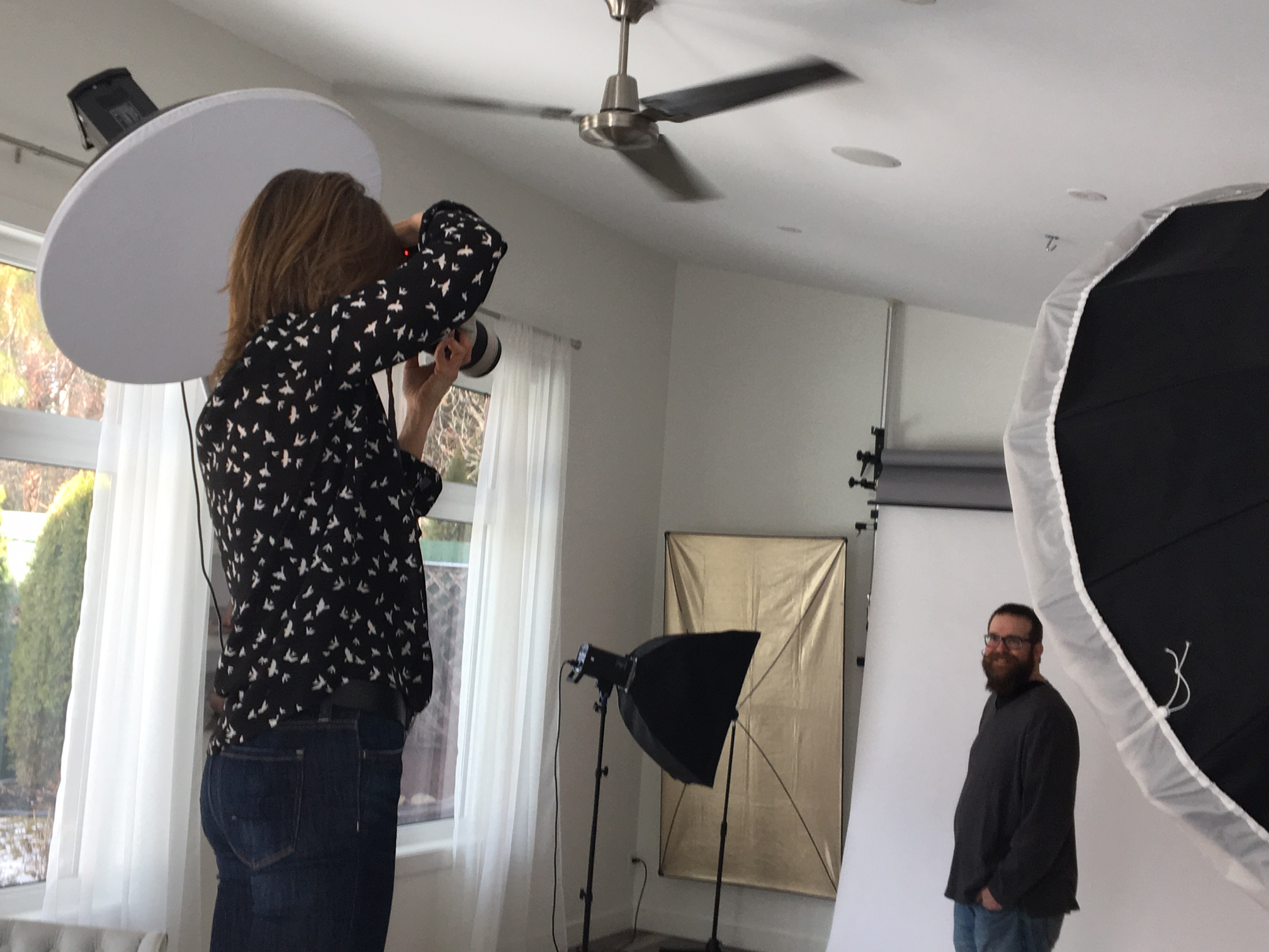 female photographer taking business headshot portrait photos in photography studio with windows