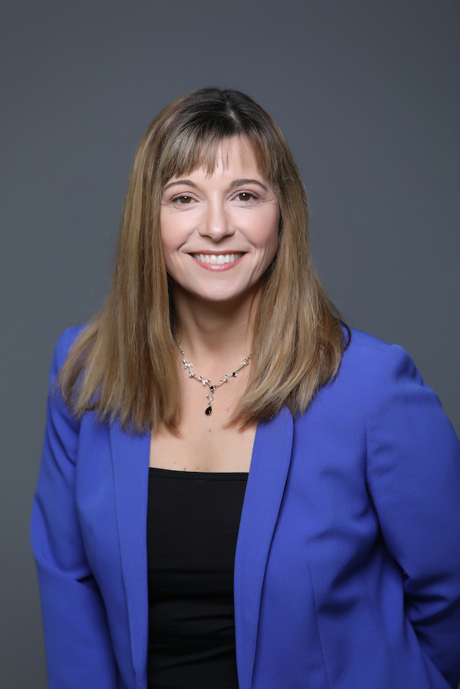 business headshot portrait of a woman wearing a blue jacket against a grey background