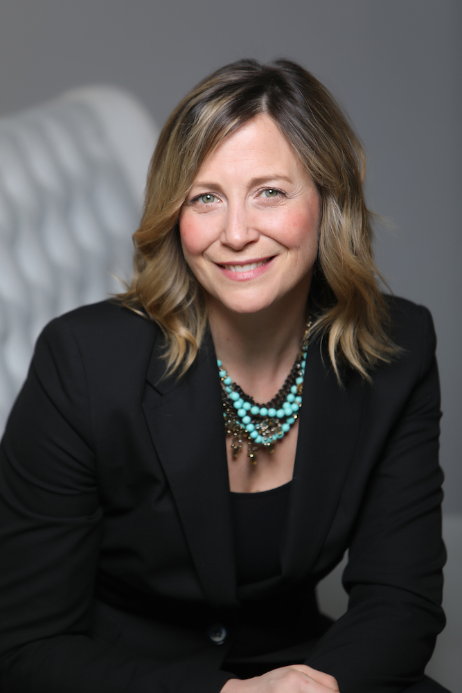 business headshot portrait of a woman in a black suit wearing a turquoise necklace against a grey background